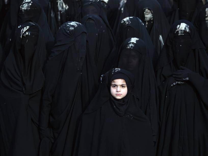 Meninas iraquianas, cobrem o rosto com véus ao participar de um desfile da Ashura, festa religiosa que lembra o martírio de Hussein, o terceiro imã dos xiitas e neto do profeta Maomé, em Bagdá - 23/10/2015