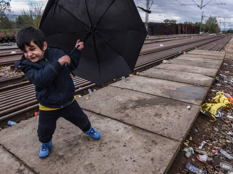 Criança segura um guarda-chuva enquanto espera por um trem com outros refugiados depois de cruzar a fronteira da Macedônia com a Sérvia perto da cidade de Bujanovac - 23/10/2015