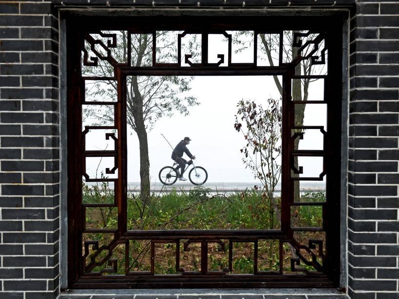 Chinês pedala ao longo das margens de um lago em Hongze, na província de Jiangsu