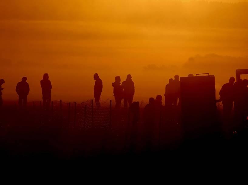 Refugiados e imigrantes são vistos enquanto esperam para atravessar a fronteira da Grécia com a Macedónia, perto da aldeia grega de Idomeni. De acordo com a ONU mais de meio milhão de refugiados e migrantes chegaram pelo mar na Grécia este ano - 27/10/2015