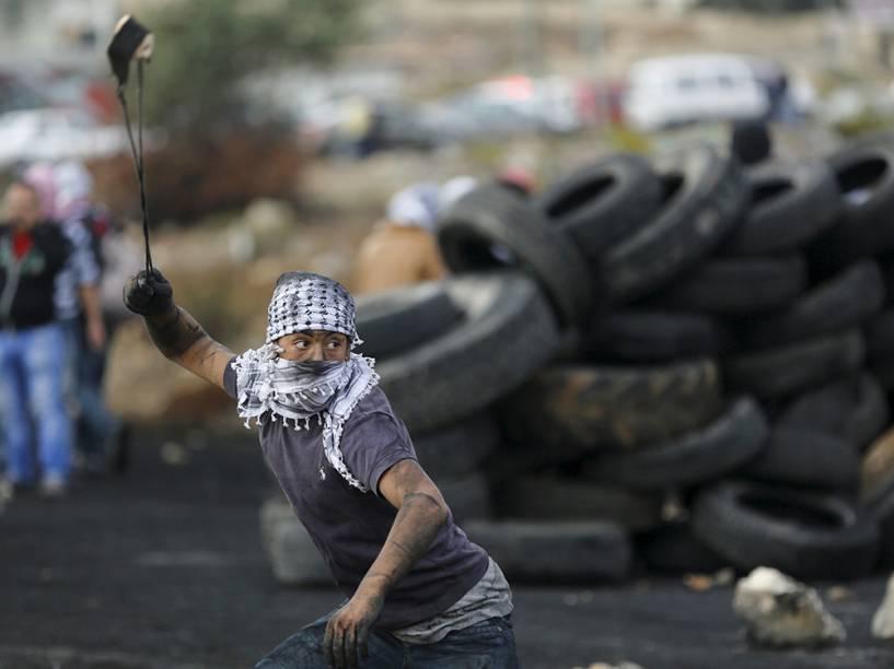 Manifestante palestino joga pedras em tropas israelenses durante confrontro próximo a um assentamento judeu em Ramallah - 27/10/2015