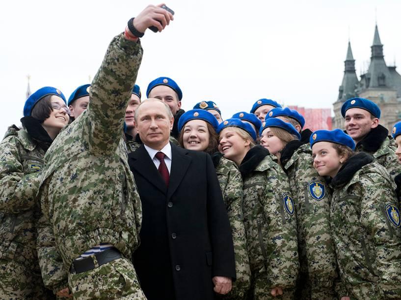 Jovens ativistas fazem selfie com o presidente russo, Vladimir Putin (ao centro), na praça Vermelha, em Moscou, durante as celebrações do Dia da Unidade Nacional. A data comemora o 403º aniversário da expulsão das forças de ocupação polonesas do Kremlin em 1612