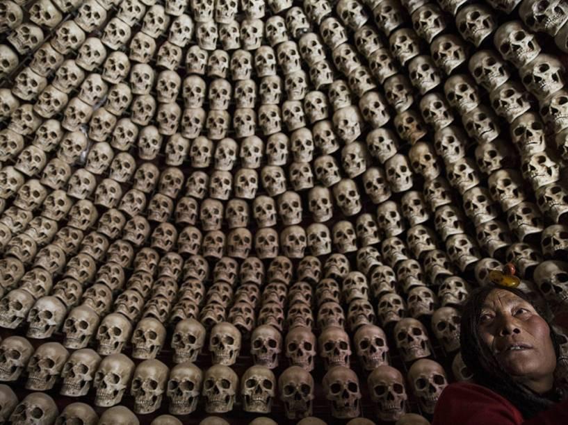 Tibetana em uma sala para enterros, decorada com crânios humanos falsos, perto do vale Larung localizado a cerca de 3700 metros acima do nível do mar