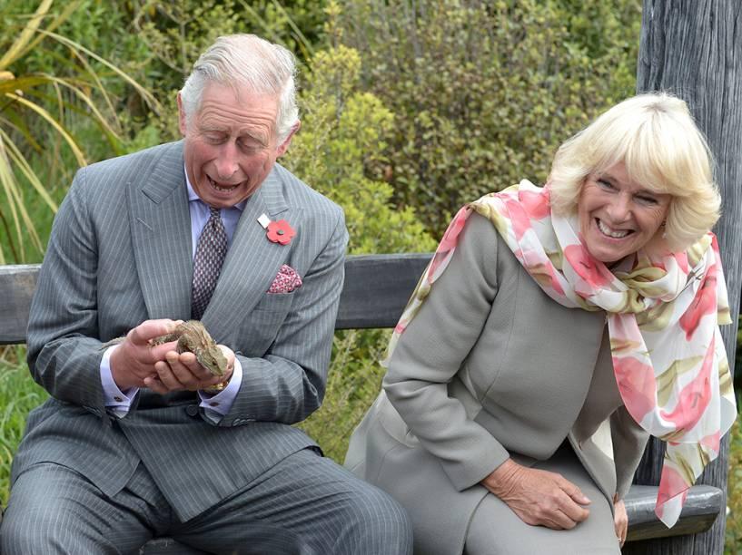 O príncipe Charles segura um lagarto tuatara durante uma visita ao santuário Orokonui Eco, perto de Dunedin, na Nova Zelândia