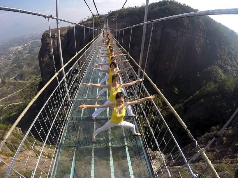 Mulheres praticam ioga em uma ponte de vidro no National Geo-parque Shiniuzhai, na China