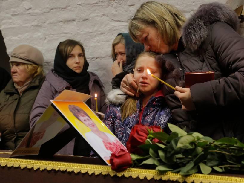 Criança chora durante cerimônia para Nina Lushchenko, vítima da queda do avião russo no Egito, em um cemitério de São Petesburgo, na Rússia. O Airbus A321 caiu no sábado (31), pouco depois de decolar, matando as 224 pessoas a bordo
