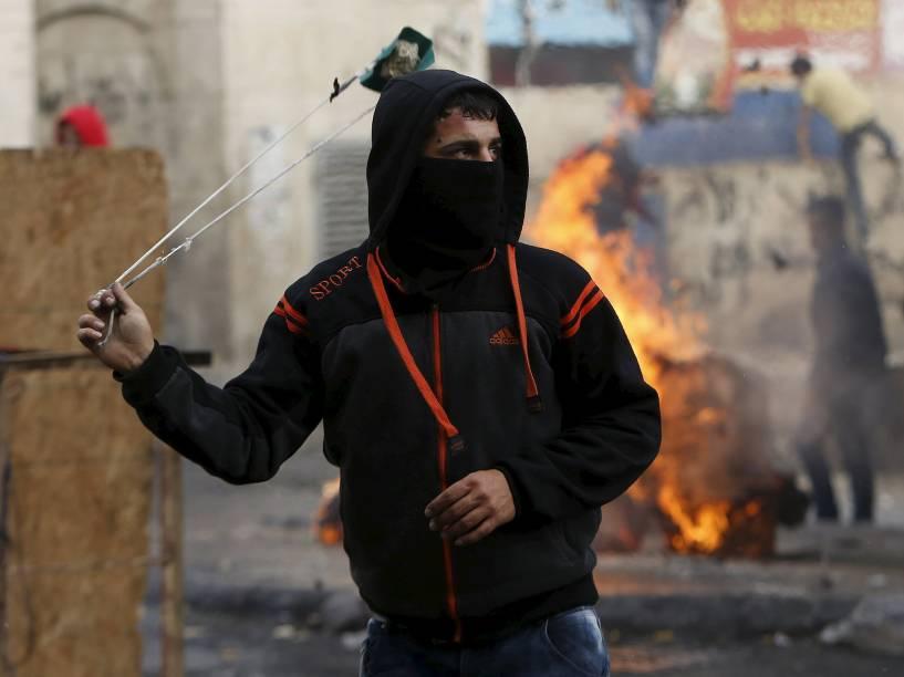 Palestino lança pedra contra forças de segurança israelenses durante confrontos no centro da cidade de Hebron, na Cisjordânia, nesta quinta-feira (05)
