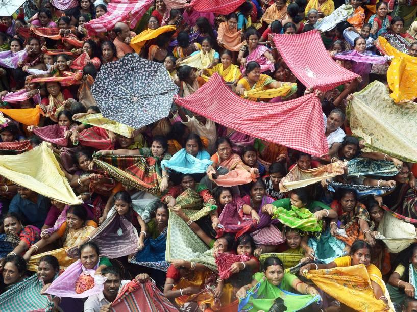 Devotos hindus recolhem punhados de arroz distribuídos pela autoridade de um templo por ocasião do festival do Annakut no templo Radha Madhav em Calcutá, na Índia - 12/11/2015