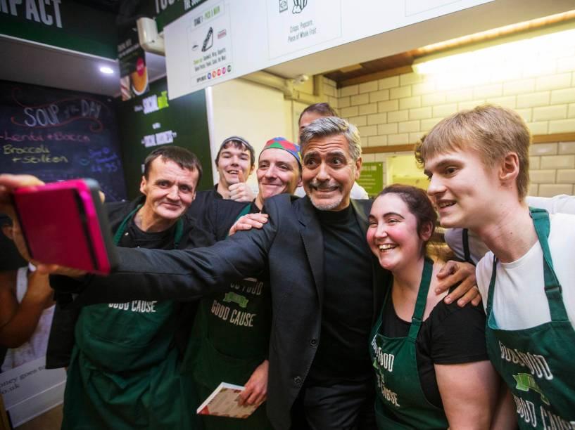 O ator George Clooney posa para foto com ex-moradores de rua que hoje são funcionários de uma cafeteria beneficente em Edimburgo, na Escócia - 12/11/2015