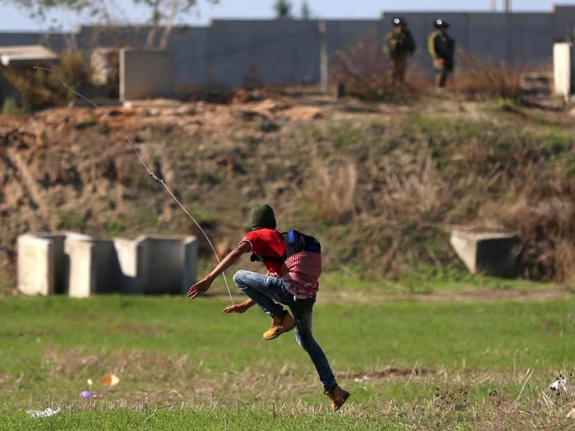 Manifestante palestino usa uma funda para jogar pedras em tropas israelenses, na Cisjôrdania - 12/11/2015