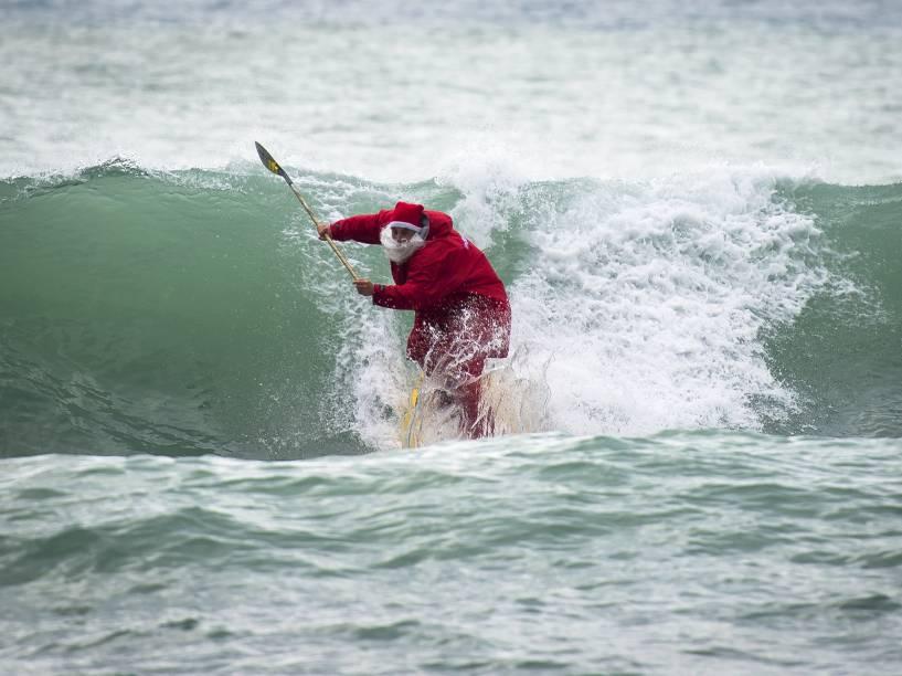 O surfista Federico Piccinaglia pega onda vestido de Papai Noel, em Levanto, na Itália - 04/12/2015
