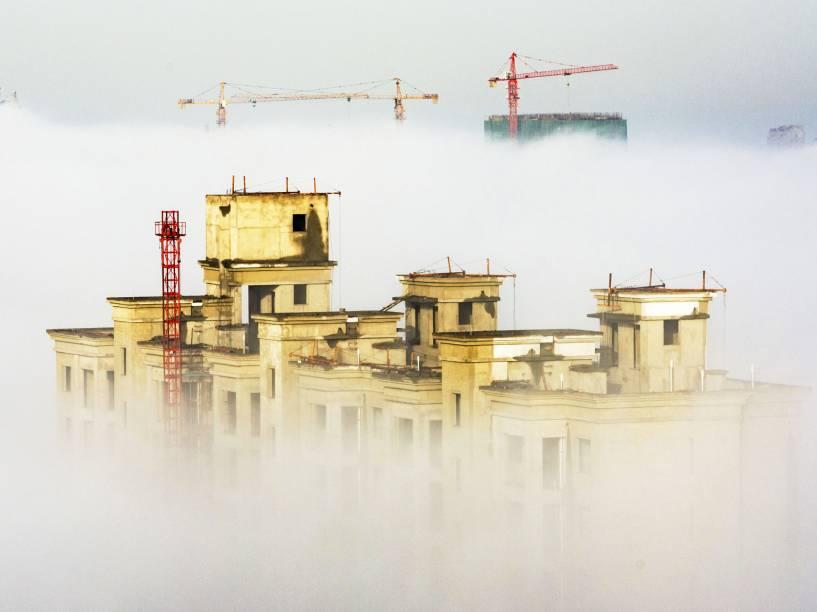 Guindastes e edifícios residenciais em construção são vistos em meio à névoa em Anyang, na província de Henan, China - 02/12/2015