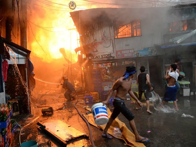 Bombeiro conta com a ajuda de moradores para apagar um incêndio em uma favela próxima a uma prisão em Manila, nas Filipinas. Centenas de presos foram evacuados e milhares de pessoas ficaram desabrigadas - 04/12/2015