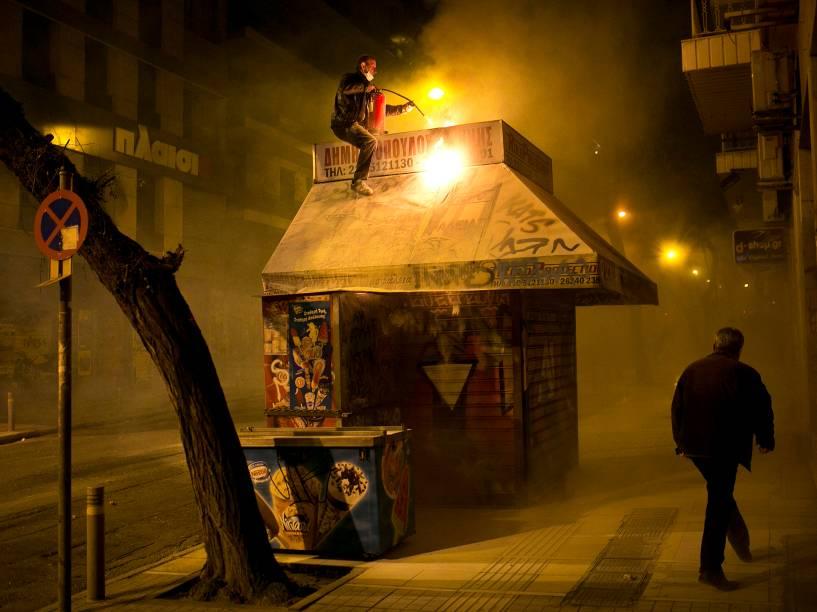 Vendedor apagou as chamas em seu quiosque durante confrontos entre a tropa de choque e manifestantes em Atenas, Grécia. O confronto aconteceu devido ao aniversário de 7 anos da morte de um garoto de 15 anos pelas mãos de policiais