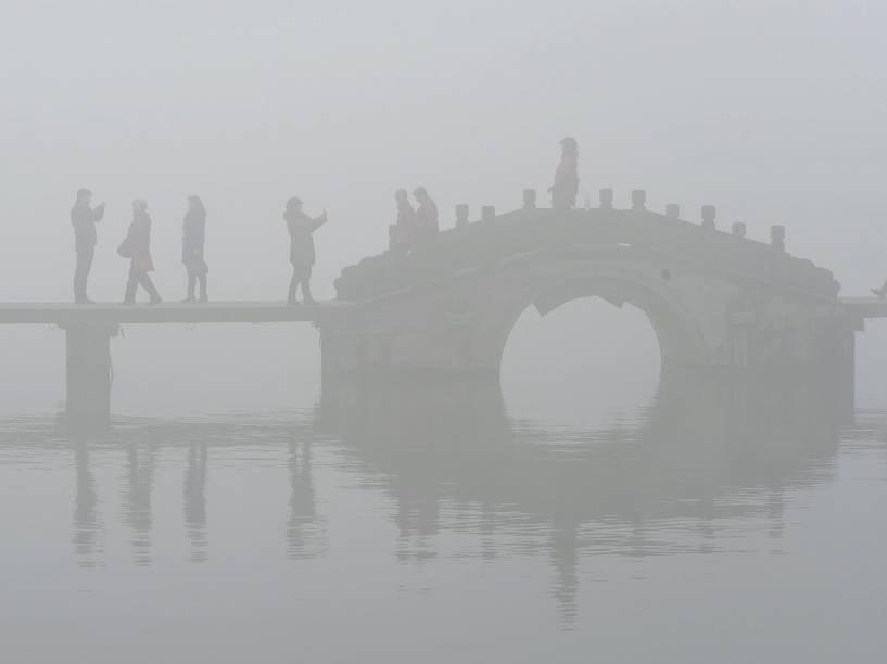Em Hangzhou, na China, turistas andaram por uma ponte sobre o Lago Oeste em meio a uma densa neblina e poluição atmosférica