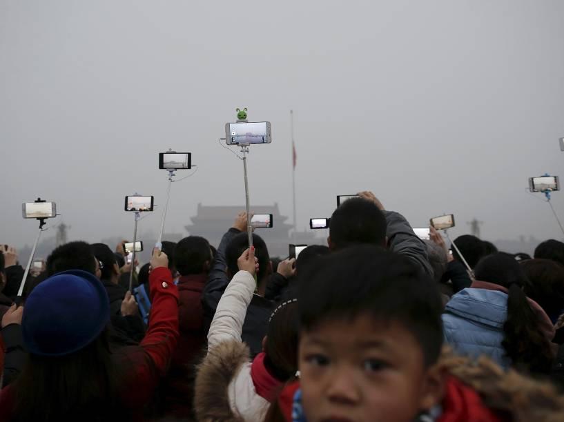 """Chineses durante uma cerimônia de hasteamento da bandeira em meio a fumaça pesada na Praça Tiananmen. Pequim está em """"alerta vermelho"""" para a poluição do ar"""