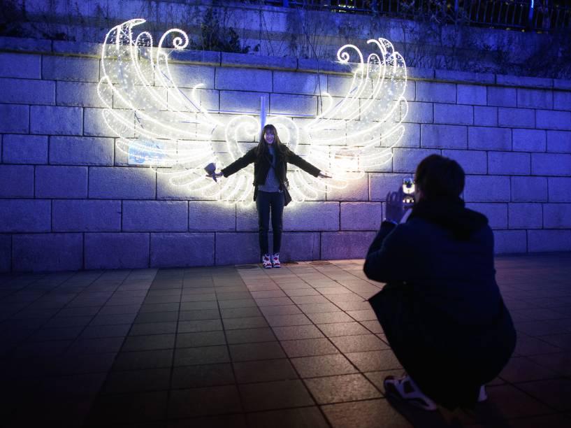 Mulher posa para foto em meio à decorações de Natal no centro de Seul, Coreia do Sul - 17/12/2015