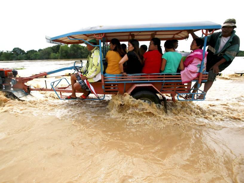 Ao norte de Manila, nas Filipinas, passageiros viajam em trator adaptado para cruzar estrada inundada após a passagem do tufão Melor pelo país. De acordo com a imprensa local, mais de 60 mil famílias ficaram desabrigadas - 17/12/2015