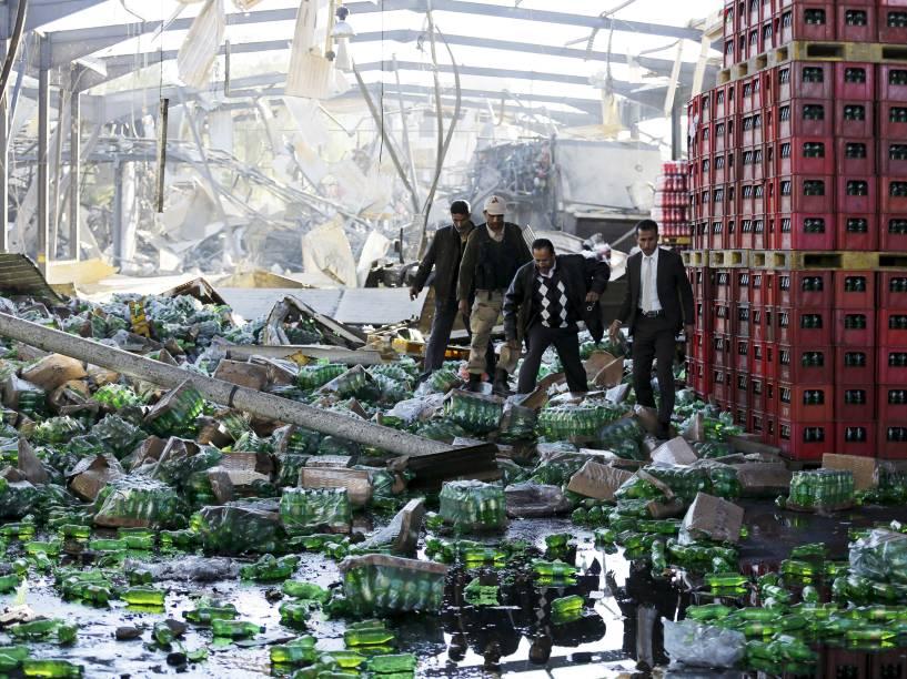 Funcionários observam o local onde uma fábrica de bebidas da Coca-Cola foi atingida por ataques aéreos em Sanaa, capital do Iêmen - 30/12/2015