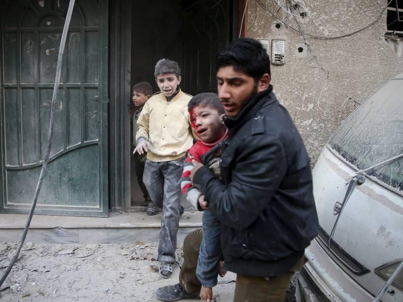 Homem carrega criança ferida durante ataque de forças leais ao presidente da Síria, Bashar al-Assad, na cidade de Douma - 30/12/2015
