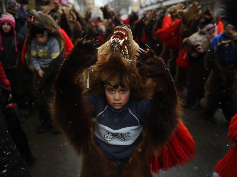 Criança usa a pele de um urso durante uma parada para afastar os maus espíritos do ano que passou, na cidade de Comanesti, na Romênia - 30/12/2015