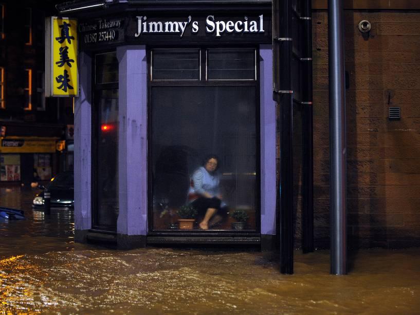 Mulher sentada em um restaurante chinês observa a inundação pela janela, em Dumfries, Escócia - 30/12/2015