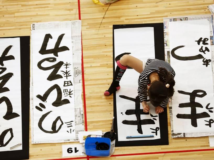 Menina participa de um concurso de caligrafia que reúne mais de 3 mil competidores para criar mensagens e desejos para o Ano Novo em Tóquio, no Japão - 05/01/2016