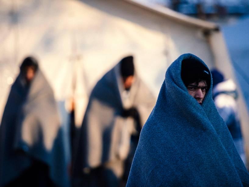 Refugiados se aquecem com cobertores enquanto aguardam um ônibus em um acampamento de registros na cidade sérvia de Presevo - 20/01/2016