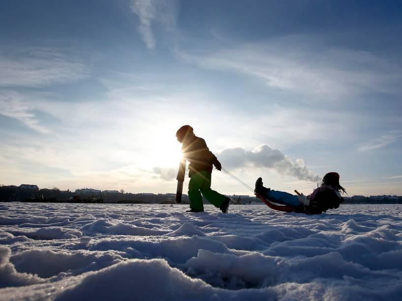 Crianças brincam de trenó sobre a neve cobriu o Theresienwiese em Munique, na Alemanha - 20/01/2016