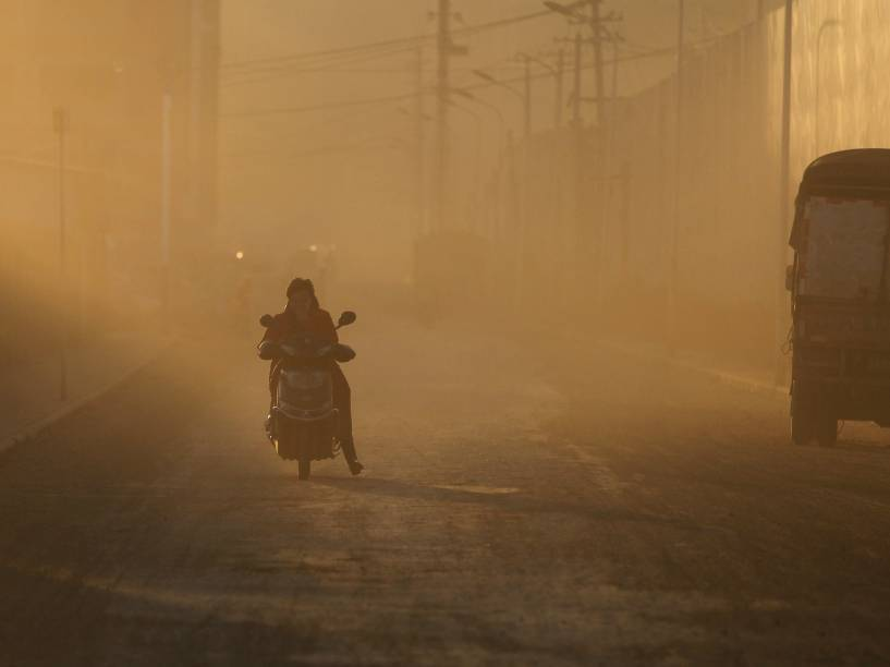 Motociclista atravessa uma nuvem de poeira, perto das obras de construção de novos complexos residenciais em Kunming, na província chinesa de Yunnan - 20/01/2016