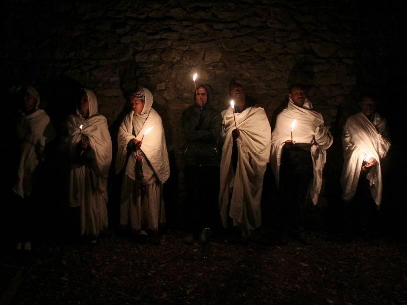 Etíopes ortodoxos seguram velas enquanto fazem orações durante a celebração do Timket que comemora o batismo de Jesus Cristo por João Batista no rio Jordão, em Gondar, Etiópia