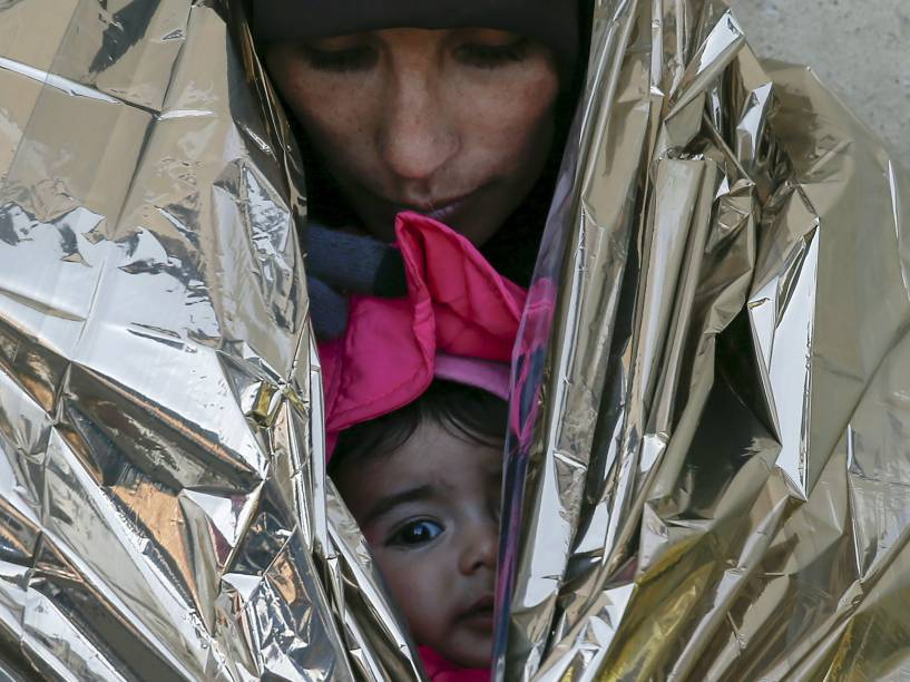 Refugiada protege sua filha em um cobertor térmico, enquanto espera por um trem para a Croácia, em uma estação em Presevo, na Sérvia - 20/01/2016