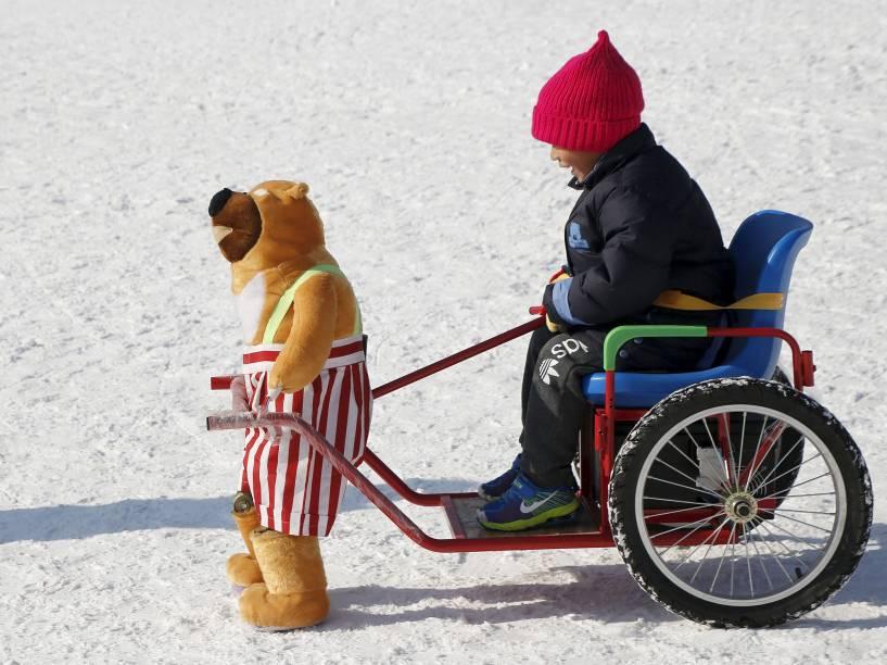 Criança se diverte em brinquedo de neve em parque de Pequim, na China, nesta segunda-feira (25)