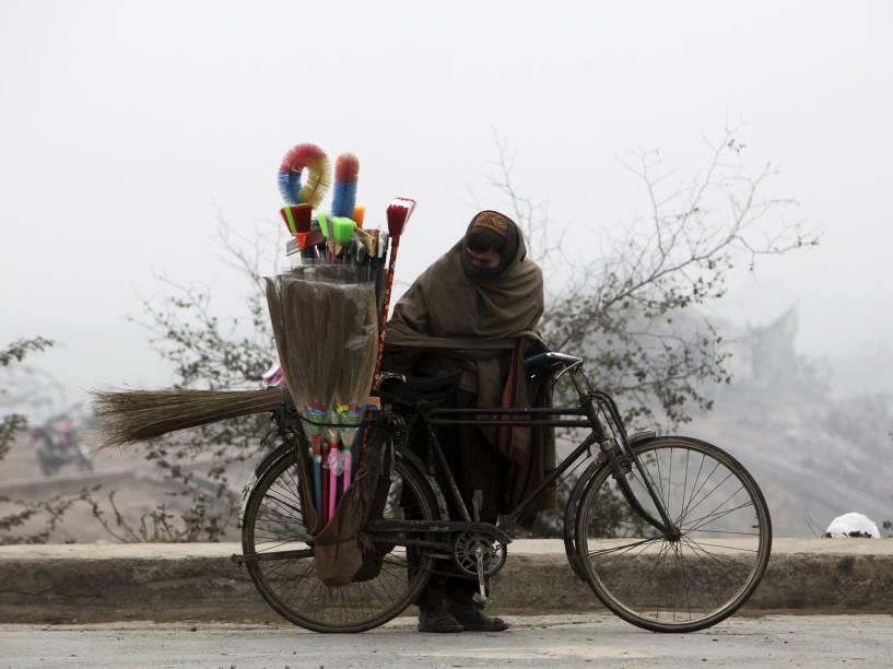 Vendedor de escovas tenta se proteger do frio em Lahore, no Paquistão