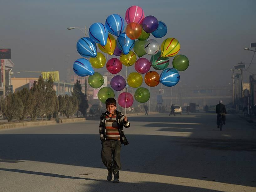 Menino vende balões em Mazar-i-Sharif, no Paquistão