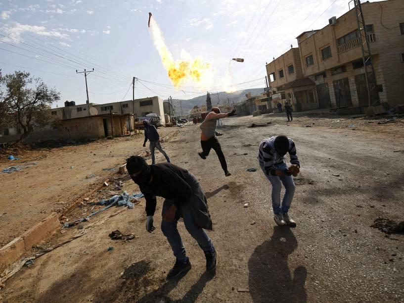 Manifestante palestino arremessa coquetel molotov, em direção às tropas israelenses, durante confronto na Cisjordânia