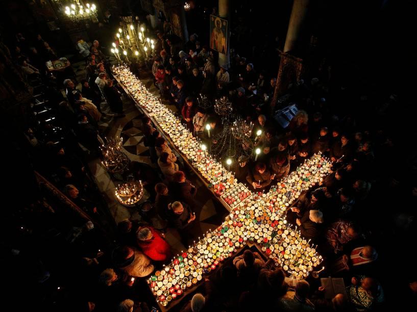 Cristãos ortodoxos se reúnem em torno de velas presas a frascos com mel, durante uma missa na igreja da Apresentação da Virgem em Blagoevgrad, Bulgária para a celebração do dia de São Haralampi, santo padroeiro dos apicultores - 10/02/2016