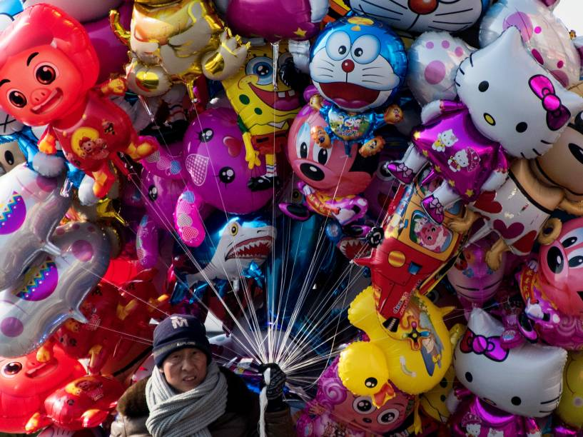 Homem vende balões nas margens do rio Yalu na cidade chinesa de Dandong na fronteira com a cidade norte-coreana de Sinuiju - 10/02/2016