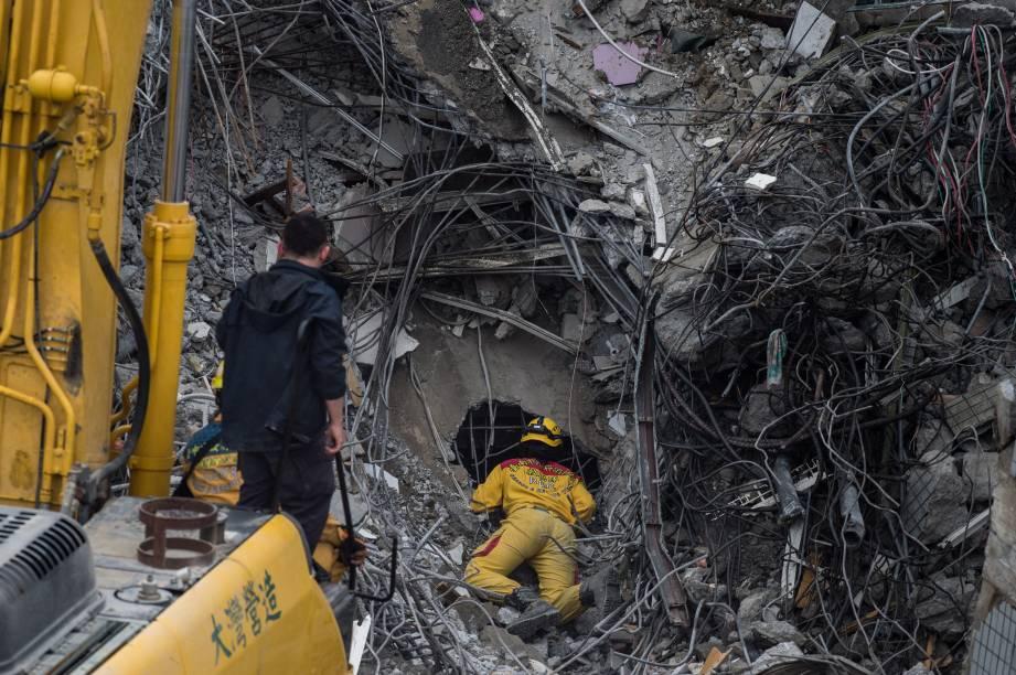 Homem da equipe de resgate observa buraco em meio aos escombros de edifício que desabou após forte terremoto no último sábado (6) na cidade de Tainan, em Taiwan, na esperança de ainda encontrar sobreviventes. A procuradoria de Tainan ordenou a detenção dos construtores do edifício. O Ministério Público acusa de negligência profissional o presidente da construtora que ergueu o prédio