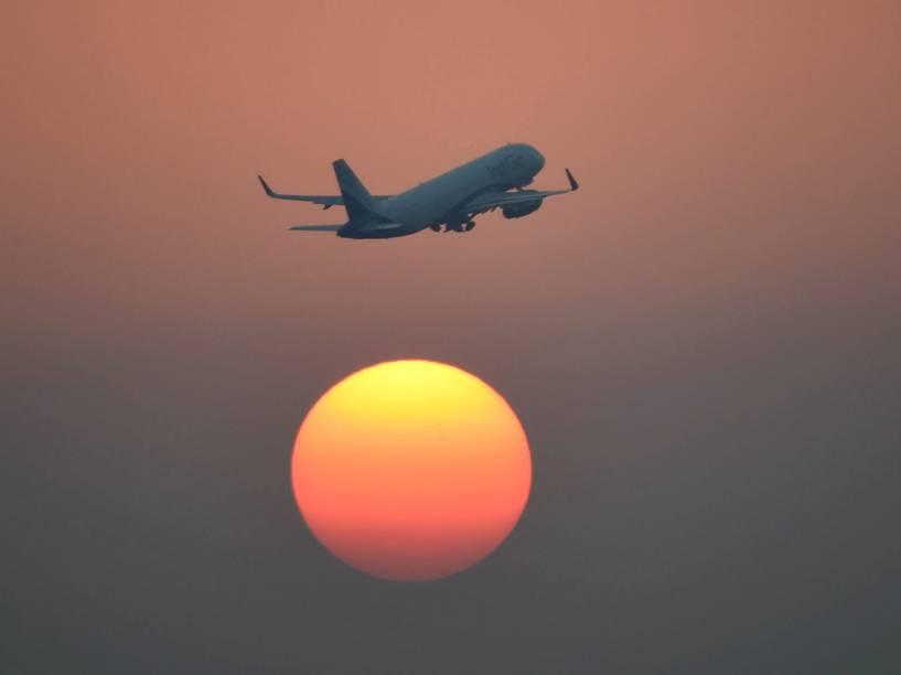 Avião decola no pôr-do-sol em Nova Délhi, na Índia
