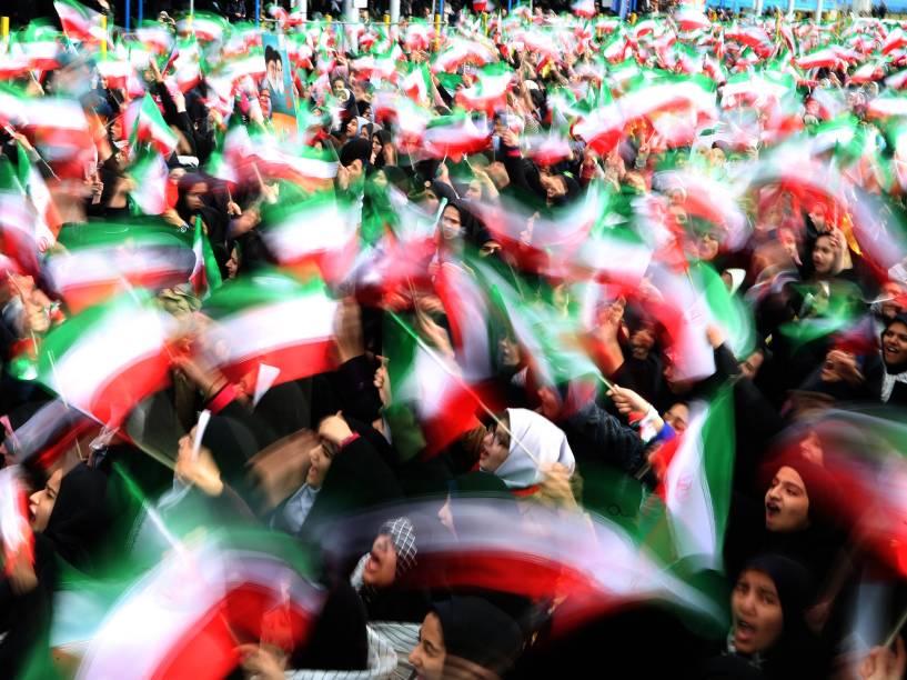 Estudantes iranianos balançam bandeiras, durante celebrações dos 37 anos da Revolução Iraniana, na Praça da Liberdade, no Irã