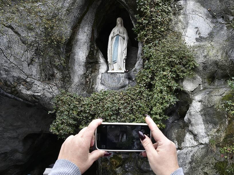 Peregrino faz uma fotografia da estátua da Virgem Maria, dentro da gruta de Massabielle, no sul da França