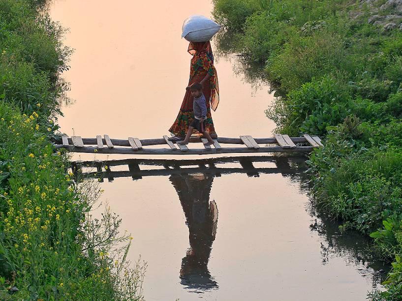 Mulher dá sua mão para um garoto, ao atravessar uma ponte improvisada feita de bambu, em um canal, na cidade de Allahabad, na Índia