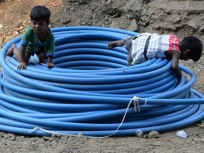 Crianças indianas brincam em meio a um rolo de tubulação à beira de uma rodovia em Mumbai