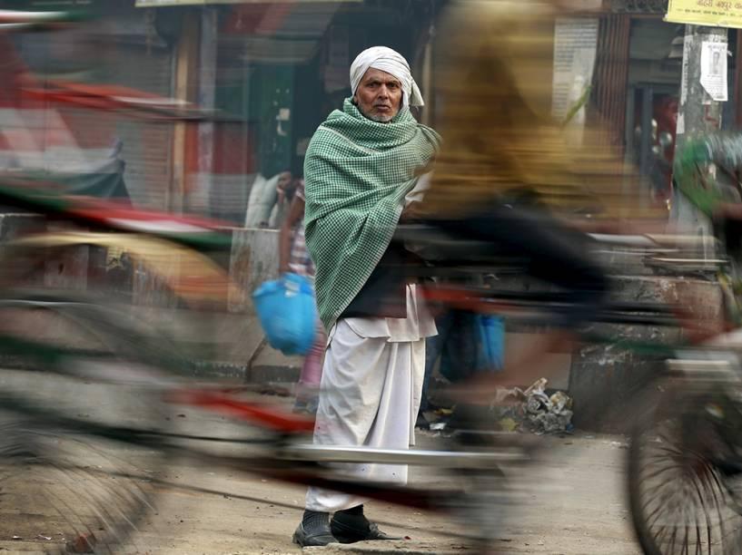Riquixá passa em frente a um homem em mercado movimentado de Déli, na Índia