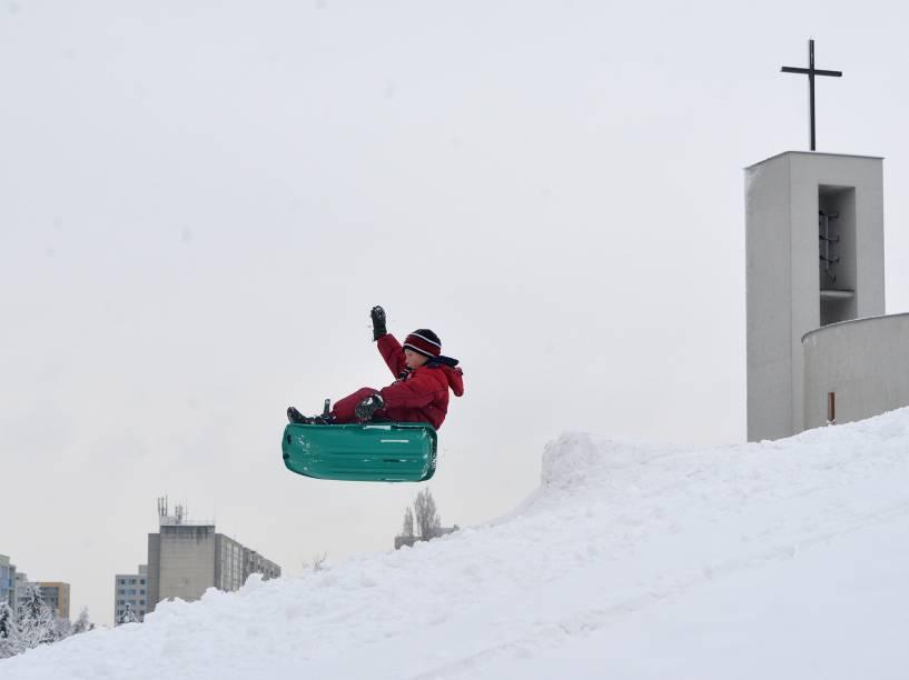 Criança brinca em um parque coberto de neve em Praga, na República Tcheca