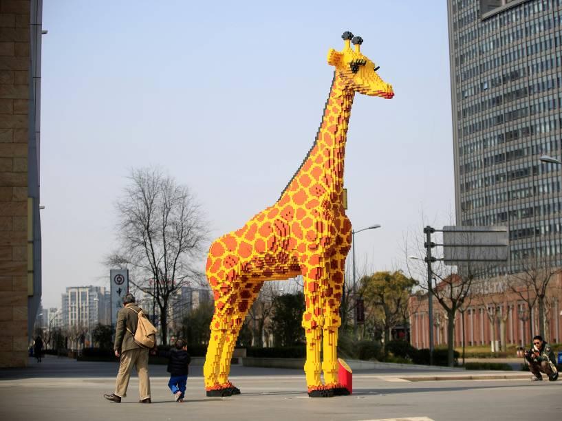 Uma girafa de 6m de altura, feita de Lego, é fotografada ao lado de um shopping center em Xangai, netsa terça-Feira (01)