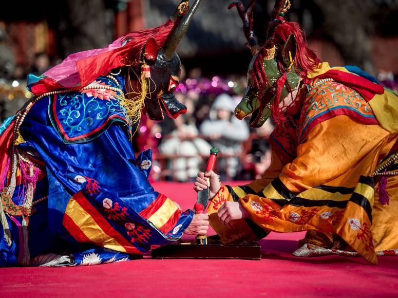 Monges budistas tibetanos vestidos de monstros participam de uma celebração religiosa durante festival em Pequim, na China