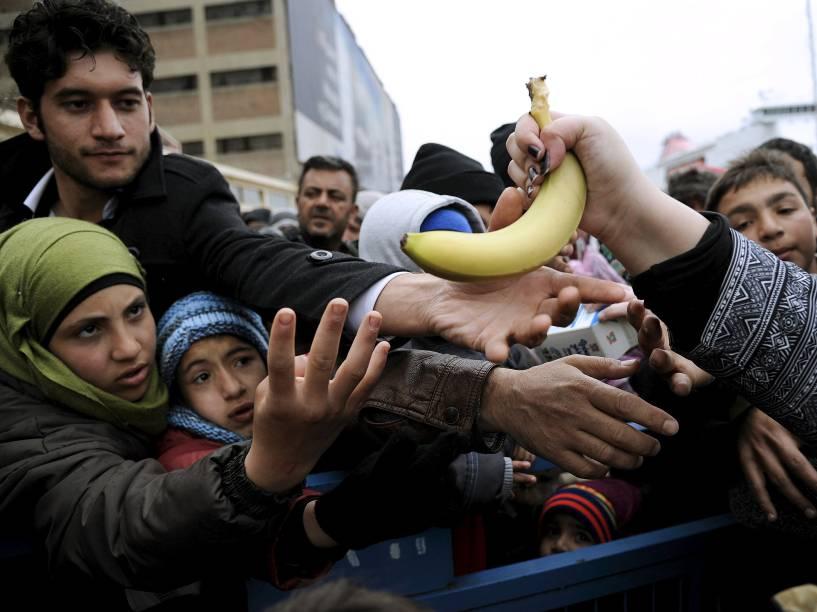 Imigrantes chegam para receber comida entregues por voluntários em acampamento de refugiados em Piraeus, Grécia<br>