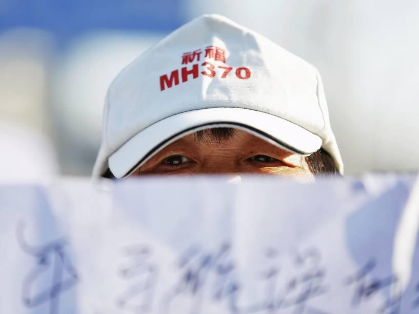Familiar de passageiro do voo MH370 da Malaysia Airlines segura cartaz durante cerimônia em templo em Pequim, China. Nesta terça-feira faz dois anos que o avião com 239 passageiros desapareceu pouco depois de decolar do aeroporto de Kuala Lumpur